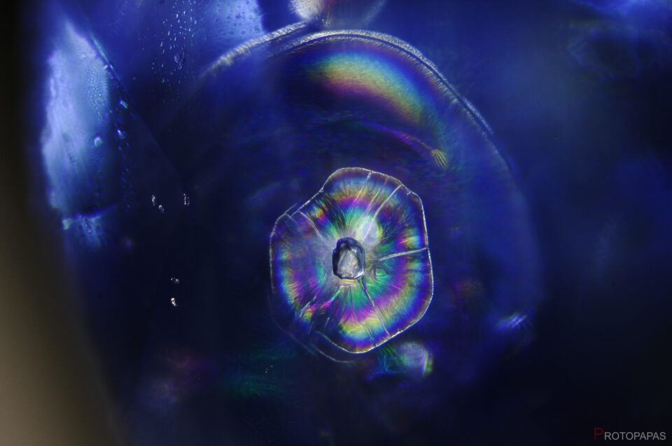 Crystal surrounded by an iridescent discoid fracture in heated Sapphire