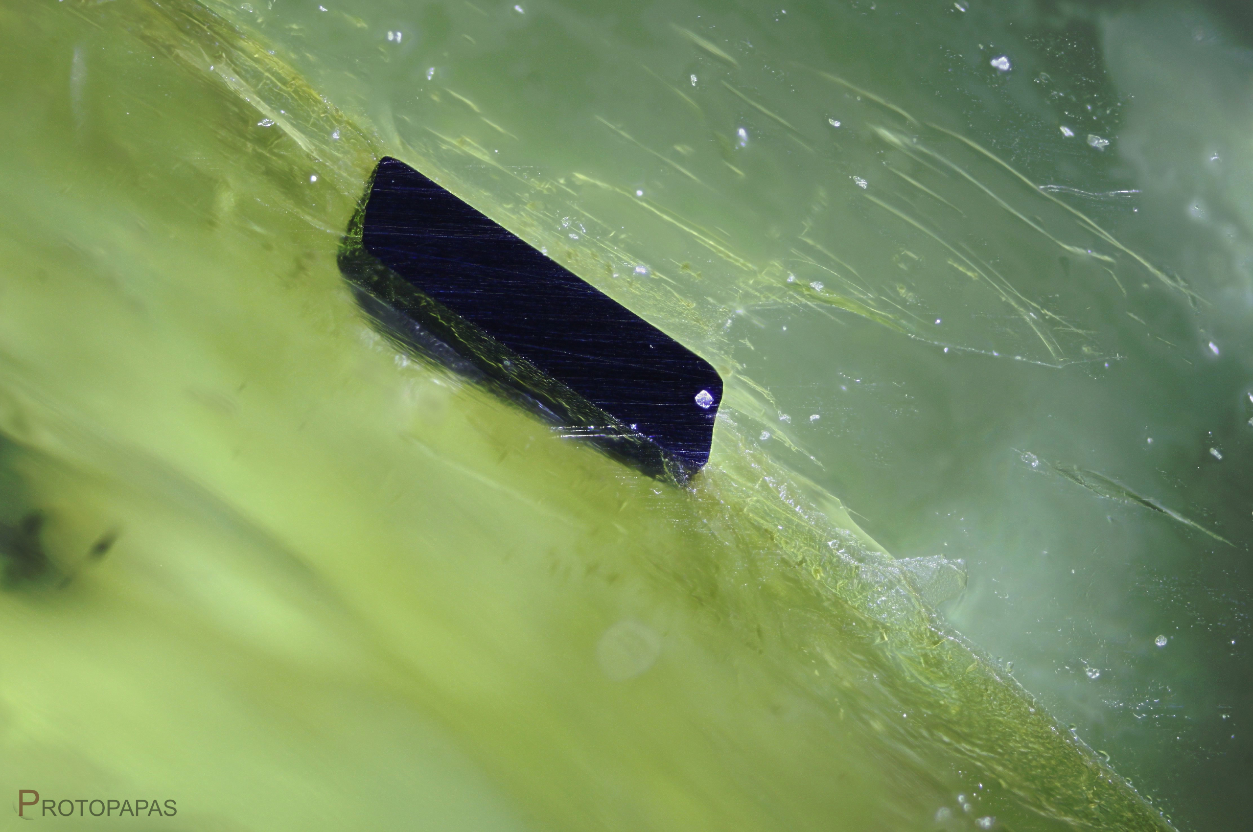 Sawed Chromite crystal on the surface of a Peridot