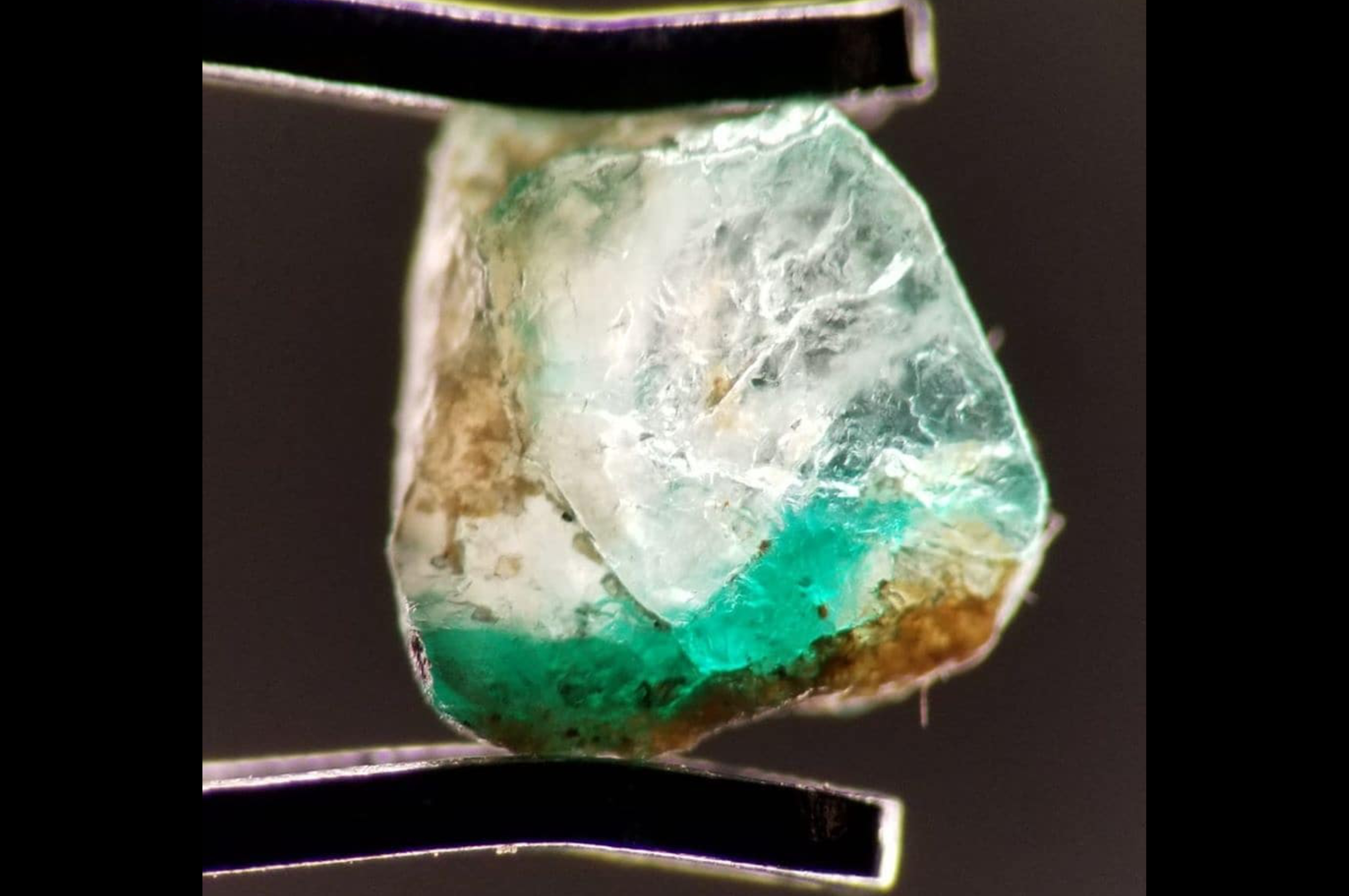 Inclusions, color zoning and perhaps old oil in rough emerald from Swat, Pakistan. Photo by Fahad Abbas Sheikh