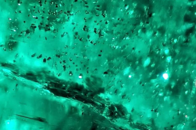 Blackish high relief mineral inclusions surrounded by internal fractures and numerous liquid inclusions in Emerald from Swat. Photo by Fahad Abbas Sheikh